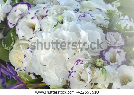 Rich white hydrangea, delicate cream roses, purple eustoma, lush leaves in a beautiful decoration. Big bouquet of fresh flowers on luxury wedding table. Summer background. - stock photo