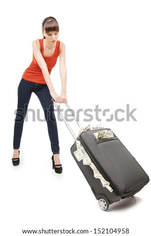 Rich woman. Beautiful young woman carrying a suitcase full of money while isolated on white