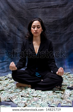 Rich woman meditating while sitting in money isolated on a dark background - stock photo