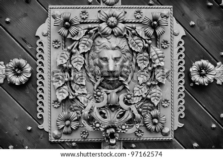 richly decorated door knocker black and white - stock photo