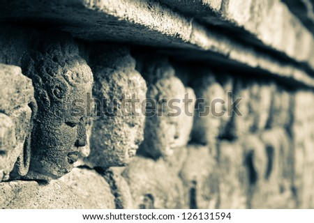 Richly decorated stone walls of Buddhist monument Borobudur in Java, Indonesia. - stock photo