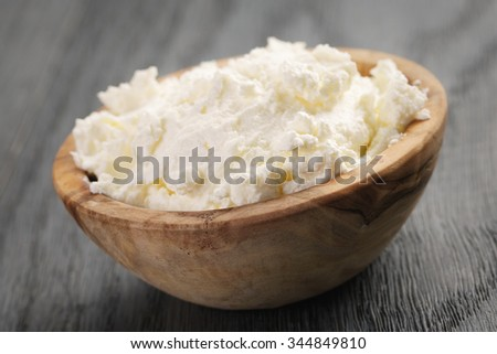 ricotta cheese in wooden bowl on old table