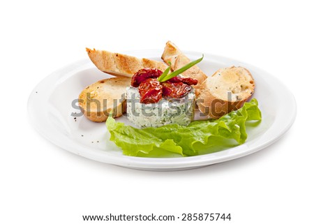 Ricotta salad decorated with sun-dried tomatoes and lettuce, served with croutons, isolated on white background. - stock photo
