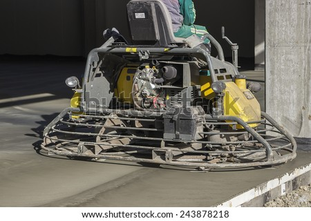 Ride on machine with trowels and worker, flat concrete floor. Double power trowel finishing concrete floor. At construction site. - stock photo