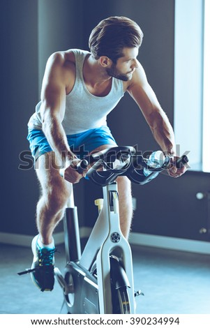 Ride to success. Young handsome man in sportswear cycling at gym - stock photo