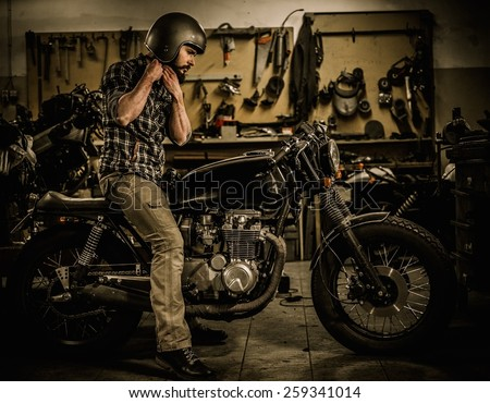 Rider and his vintage style cafe-racer motorcycle in customs garage  - stock photo