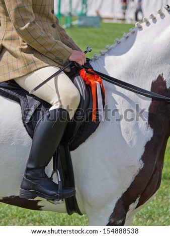 Rider and horse displaying rosette for a minor placing in an equestrian event in UK - stock photo