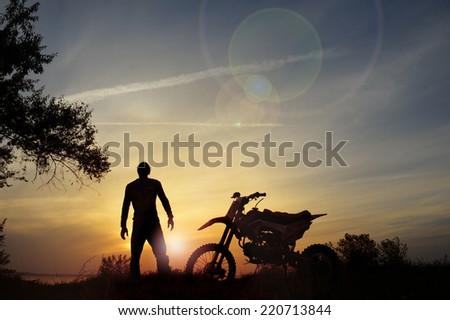 rider and the bike at sunset. - stock photo
