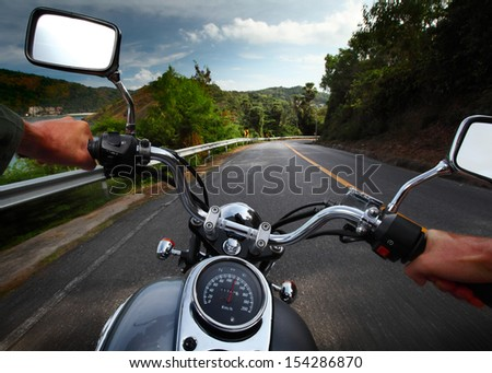 Rider driving motorcycle on a rural road in a mountains - stock photo