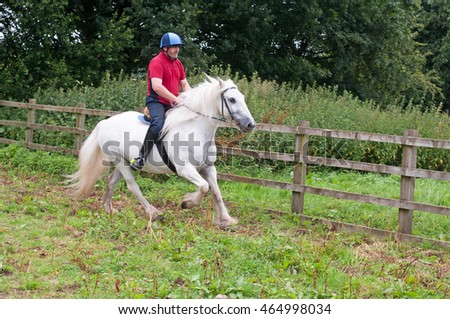 Rider enjoying a canter on a lovely grey horse