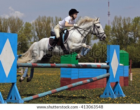 Rider jumping on back of a grey horse - stock photo