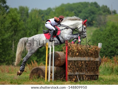 Rider jumping with horse over obstacle - stock photo