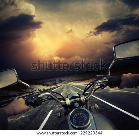Rider on the motorcycle moving towards dark storm clouds on the asphalt road - stock photo