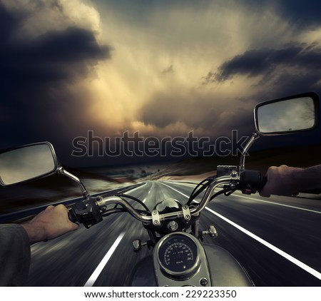 Rider on the motorcycle moving towards dark storm clouds. Road and sky are motion blurred - stock photo
