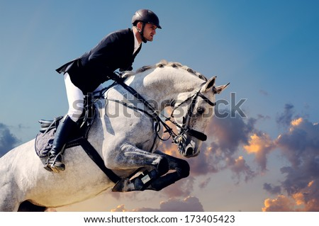 Rider on white horse in jump on the background of sunset sky