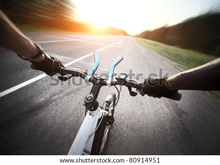 Rider's hands in gloves on a bicycle handlebar. Motion blurred