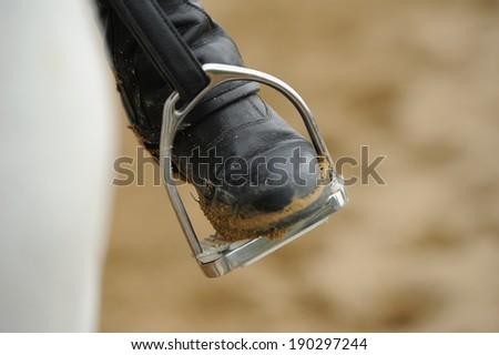 Rider's leg in the stirrup - stock photo