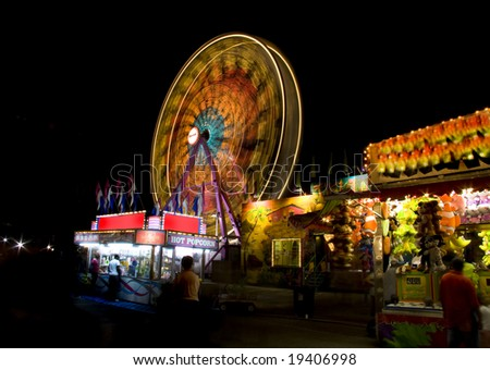 Rides and food stands at the state fair. - stock photo