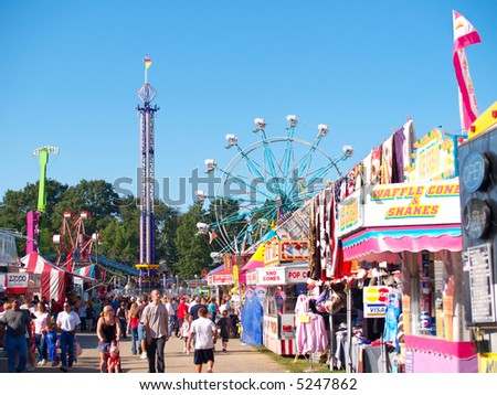 Rides, concessions, and crowds at a county fair - stock photo