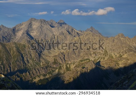 Ridge of mountains with rocks in last sun rays - stock photo