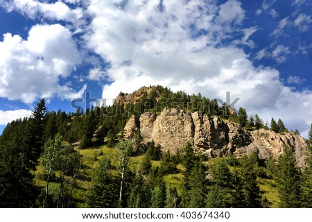 Ridge on top of a mountain in the Absaroka Mountain range is rugged and steep.  Landscape image is complete with fluffy white clouds and blue sky. - stock photo