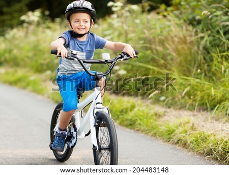 Riding a bicycle for the first time on a country road concept for healthy lifestyle, exercising and road safety - stock photo