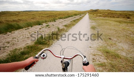 Riding a bike in the summer in the dunes of the Frisian Island of Vlieland.  - stock photo