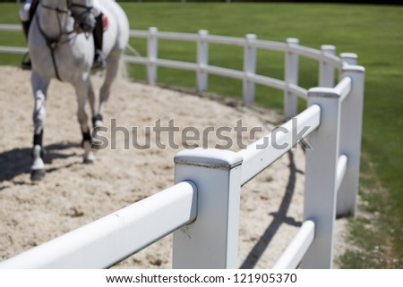 Riding a white horse. Horse riding track with sand on the ground, and a white horse in the background. Selective focus on the fence - stock photo