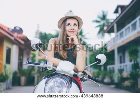 Riding dreaming. Outdoor portrait of pretty young woman in hat sitting on scooter. - stock photo