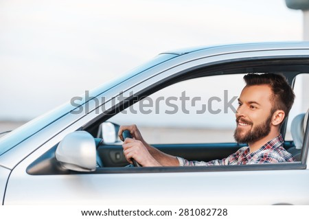 Riding his new car. Side view of handsome young man driving his car and smiling  - stock photo