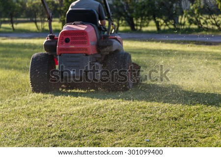 Riding Lawn Equipment with operator for periodically garden upkeep - stock photo