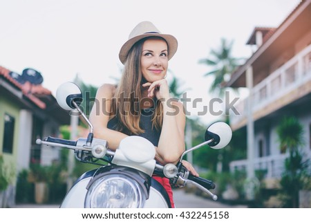 Riding lifestyle. Outdoor portrait of pretty young woman in hat sitting on scooter. - stock photo