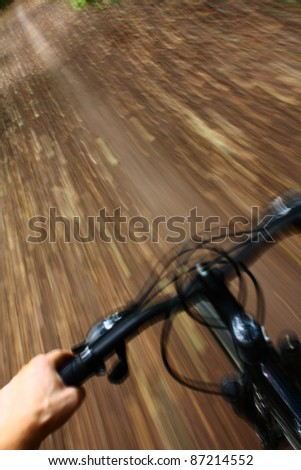 Riding mountain bike in forest - stock photo