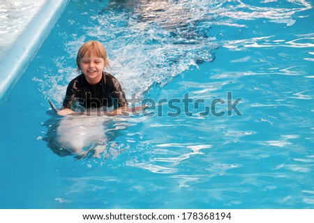 Riding on a dolphin at the dolphin therapy session