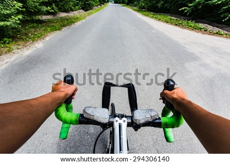 Riding on flat road asphalting in the forest. Hands on the steering wheel bicycle. Eye view from cyclist head - stock photo