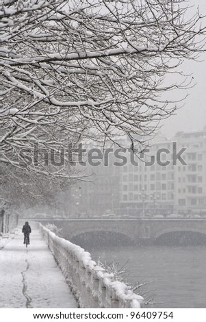 Riding under the snow A woman rides a bicycle under the snow in San Sebastian, Spain - stock photo