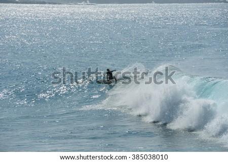 Riding Waves - Surfer enjoying riding on big blue waves in Honolua Bay at north coast of Maui, Hawaii, USA. - stock photo