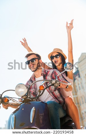 Riding with fun. Beautiful young couple riding scooter together while happy woman raising arms and smiling  - stock photo