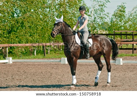 riding young woman portrait on horse in outdoor - stock photo