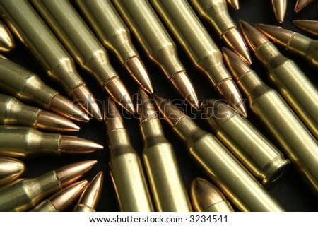 rifle and handgun bullets on a black surface - stock photo