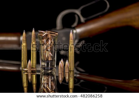 Rifle bullets and shot glass or copper and brass
