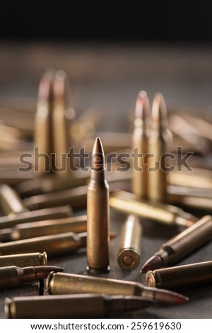 Rifle bullets on wood table with low key scene - stock photo