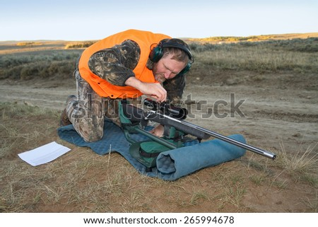 rifle hunter adjusting rifle scope - stock photo