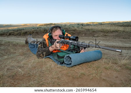 rifle hunter lying in prone position and aiming rifle - stock photo