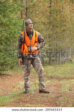 rifle hunter standing in woods - stock photo