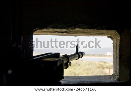 rifle ready to shoot in the embrasure in background made from landscape with lake and green - stock photo