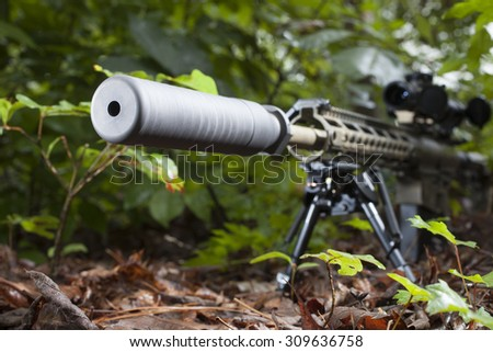 Rifle with a silencer that is in a bunch of bushes - stock photo