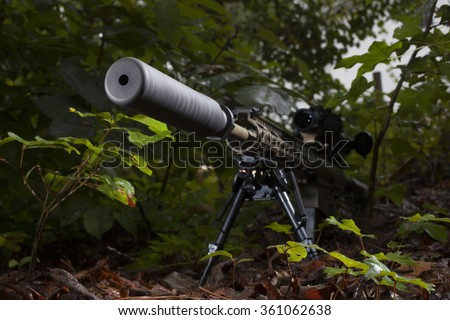 Rifle with a suppressor mounted that is in the trees - stock photo