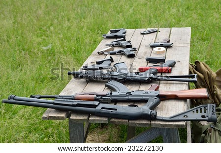 Rifles, pistols and other portable guns are laid out on the table outdoors. - stock photo