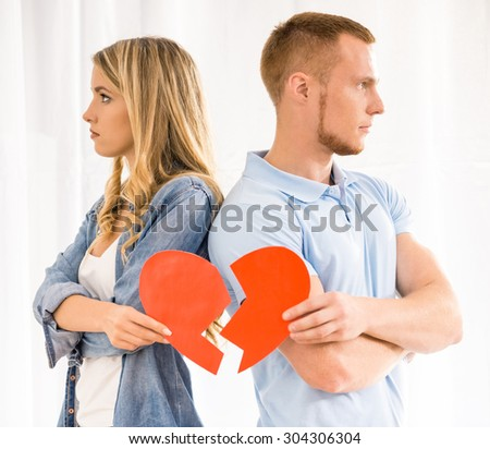 Rift in relations. Sad young couple holding broken heart. - stock photo